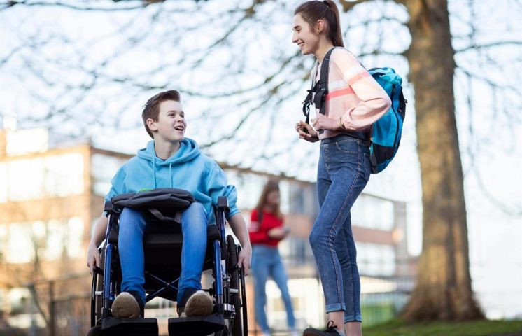 Skoleelever en i rullestol og en står